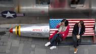 Zwei Frauen sitzen auf einer Bank vor einem Laden für amerikanische Bekleidung in Peking.