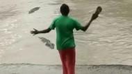 Frau vertreibt Krokodil mit einem Flip-Flop