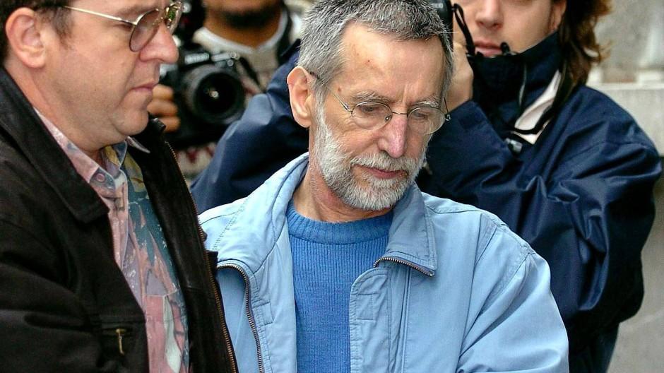 Der französische Serienmörder Michel Fourniret (mittig) wird 2004 in ein belgisches Gerichtsgebäude gebracht.