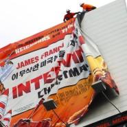 """Arbeiter entfernen in Hollywood das Werbeplakat für den von Sony zurückgerufenen Film """"The Interview""""."""