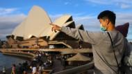 Ein Mann trägt vor dem Opernhaus in Sydney eine Atemschutzmaske.