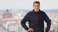 Der Triathlet und Ironman-Weltmeister Jan Frodeno posiert vor der Kulisse der Stadt Nürnberg am Rande einer Pressekonferenz zum anstehenden Triathlon.