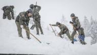 In St. Koloman, Österreich schaufeln Bundesheer-Soldaten Schnee von einem Dach.