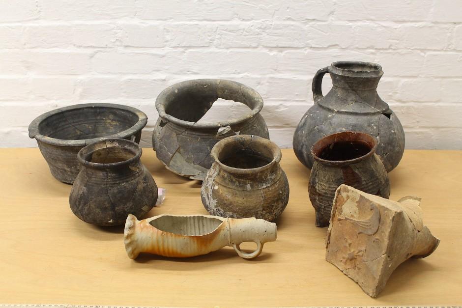 Aus den Sedimentschichten der Latrine kamen einige Keramikgegenstände zum Vorschein, darunter eine mit einem Greif verzierte Kachel (rechts unten).