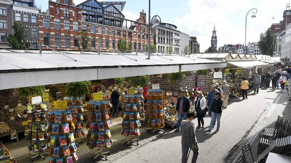 Menschen laufen am Blumenmarkt in Amsterdam entlang.