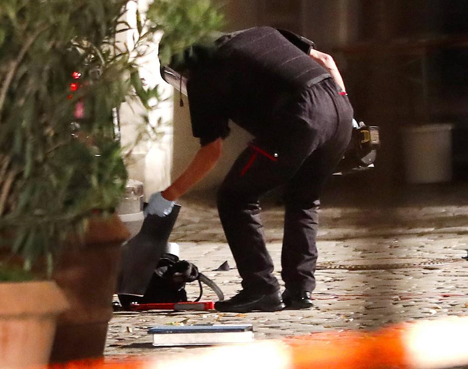Polizisten untersuchen den Rucksack, in dem der mutmaßliche Attentäter offenkundig scharfkantige Metallteile versteckt hatte