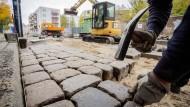 Streitpunkt Straßenbau: Ein Bauarbeiter setzt in Potsdam Pflastersteine.