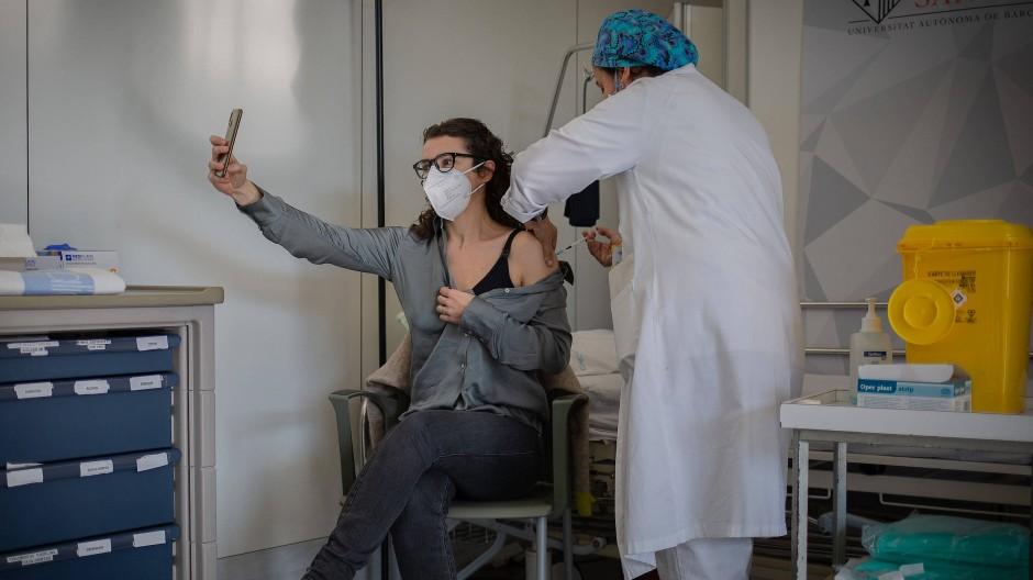 Eine Krankenschwester impft eine medizinische Fachkraft in einem Krankenhaus in Barcelona mit dem Impfstoff von Pfizer-Biontech