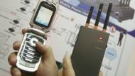 Staatschefs stören die Kommunikation mit schwererem Gerät. Dieser Störsender (rechts) eignet sich eher für den privaten Gebrauch - Aufnahme von einer Messepräsentation mit Handy (links)