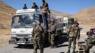 Syrische Soldaten kontrollieren am Grenzübergang Zamrany einen Lastwagen mit Flüchtlingen.