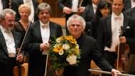 Sir Simon Rattle, Chefdirigent in der Berliner Philharmonie, nimmt mit Blumen in der Hand den Applaus des Publikums entgegen.
