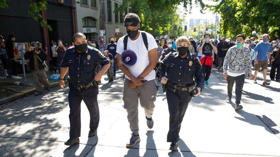 Seattle, 11. Juli 2020: Ein Demonstrant begleitet die leitenden Polizeibeamten Adrian Diaz (links) und Deanna Nollette zu ihrem Revier in der sogenannten Autonomen Zone von Capitol Hill. Das Revier war während der Proteste nach dem Tod George Floyds von der Polizei aufgegeben worden.