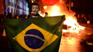 """Maske und Gegenmacht: """"Ordnung und Fortschritt"""" heißt es auf der Nationalflagge. Dieser brasilianische Demonstrant hat davon sein eigenes Verständnis"""
