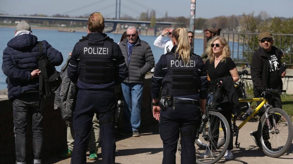 An der Düsseldorfer Rheinufer-Promenade kontrollieren Polizisten die Einhaltung der Regeln, Abstand voneinander zu halten.