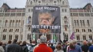 """Bei einer Demonstration Oppositioneller gegen Ministerpräsident Viktor Orban in Budapest hält ein Mann ein Schild mit der Aufschrift """"Was habe ich da getan?"""" in die Luft."""
