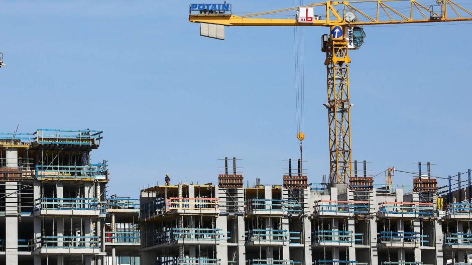 Zwei Kräne stehen vor einer Baustelle für Wohnhäuser in Hamburg. (Archivbild)