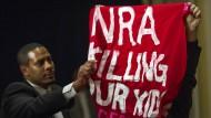 """""""Die NRA tötet unsere Kinder"""" steht auf einem der Transparente, mit denen Demonstranten am Freitag auf der Pressekonferenz der NRA gegen die Waffenlobby protestierten"""