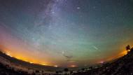 Die Milchstraße über Fehmarn in Schleswig-Holstein. Mehrere Sternschnuppen sind am klaren Nachthimmel  zu sehen.