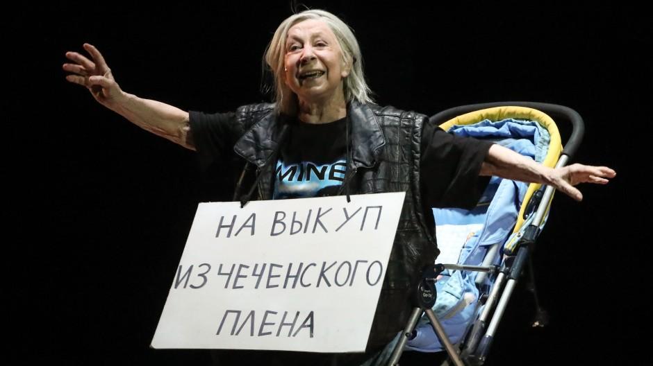"""""""Kann aus tschetschenischer Haft freigekauft werden"""" steht auf dem Pappschild, das Lija Achedschakowa als trinkfreudige Babuschka Nuria um den Hals trägt."""