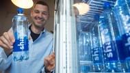 Sebastian Stricker, Gründer des Start-up-Unternehmens Share Foods GmbH, hält eine Flasche Share-Mineralwasser.