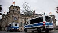 Polizeifahrzeuge stehen vor dem Reichstagsgebäude.