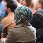 Eine Frau mit Kopftuch sitzt während einer Veranstaltung an der Uni Frankfurt im Publikum.