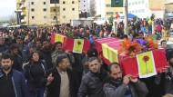 Kurdische Trauergäste tragen bei einer Beerdigung Särge von bei der türkischen Afrin-Offensive Getöteten.