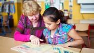 Eine Lesepatin hilft eine Schülerin beim Textverständnis.