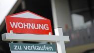 """Ein Schild mit der Aufschrift """"Wohnung zu verkaufen"""" vor einem Mehrparteienhaus in Nürnberg (Bayern)"""