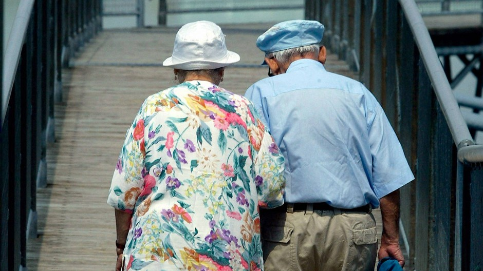 Ein Rentnerpaar geht in Freiburg spazieren.