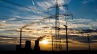 Die Sonne geht in Niedersachsen, Hohenhalmen hinter dem Steinkohlekraftwerk Mehrum, Windrädern und einer Hochspannungsleitung unter.