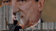 Ein Demonstrant zerreißt am 25. Januar 2011 in Alexandria ein Mubarak-Plakat