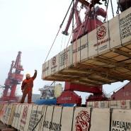 Ein Hafenarbeiter verlädt Ware auf ein Containerschiff in Lianyungang (China).