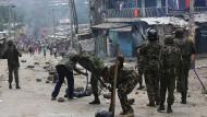 Polizisten räumen in einem Slum auf, nachdem es am Mittwoch zu Protesten gekommen ist.