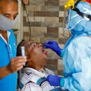 In der indischen Stadt Ahmedabad nimmt ein Arzt einen Abstrich von einem möglicherweise erkrankten Patienten.