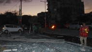 Trümmerteile übersäen nach dem Anschlag eine Hauptstraße in Mogadischu.