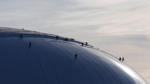 "Workers are seen on the roof of ""Bolshoy"" Ice Dome, part of the complex of facilities to be used for the Sochi 2014 Winter Olympics"