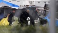 Griechische Polizisten inspizieren am Dienstagmorgen Zelte im Lager von Idomeni.