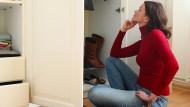 Höchste Zeit für mehr Nachhaltigkeit: Eine Frau vor übervollem Kleiderschrank.