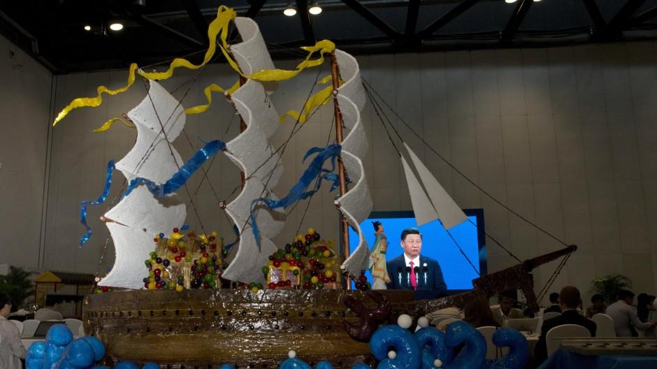 """Chinas Präsident Xi Jinping ist am 14.05.2017 auf einem Fernseher bei seiner Eröffnungsrede zur Gipfelkonferenz zur """"Neuen Seidenstraße"""" zu sehen."""