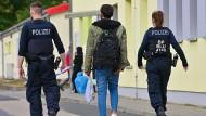 Zwei Beamte der Bundespolizei begleiten einen Flüchtling auf dem Gelände der Zentralen Erstaufnahmeeinrichtung für Asylbewerber (ZABH) des Landes Brandenburg.