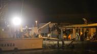 Italienische Polizisten sind im Oktober 2013 im Hafen von Lampedusa im Einsatz, nachdem ein Schlepperboot 545 Menschen mit sich in die Tiefe gerissen hat. Das Boot soll Medhane gehört haben.