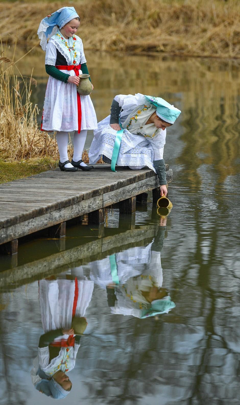 Die beiden Schwestern Aliena (l) und Leonie Huber zeigen in sorbisch-wendischen Festagstrachten in dieser nachgestellten Szene den Lausitzer Brauch vom Osterwasserholen.