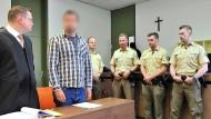 Der Angeklagte zwischen seinem Rechtsanwalt und Polizisten vor dem Landgericht München
