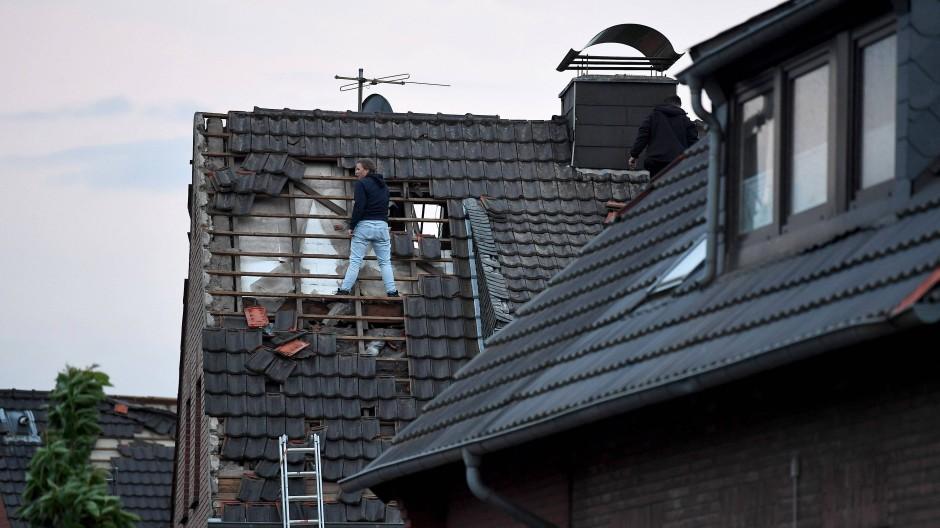 Eine Frau begutachtet die Schäden am Dach eines Hauses in Boisheim, das von dem Tornado beschädigt wurde.