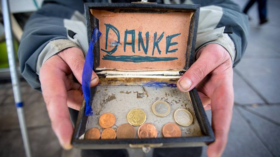 Ein Bettler bedankt sich in der Fußgängerzone für Geldspenden.