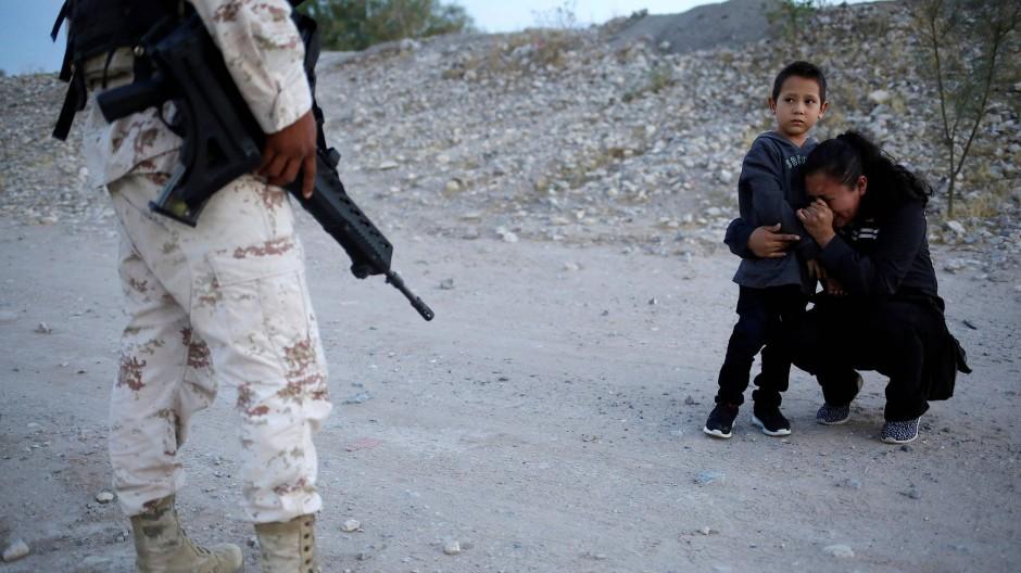 Die Migrantin aus Guatemala umgreift ihren Sohn und kniet auf dem Boden des ausgetrockneten Flussbettes. Die Waffe des Soldaten zeigt Richtung Boden.