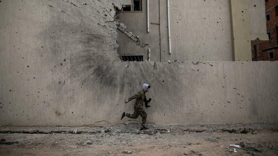 Ein Soldat der international anerkannten Regierung (GNA) geht vor Scharfschützen der Libyschen Nationalen Armee (LNA) in Deckung.