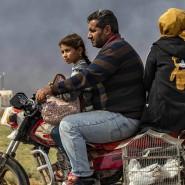 Eine Familie flieht am Samstag auf einem Motorrad aus der Region um die Stadt Ras al Ain.