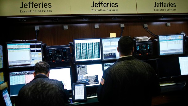 Trading specialists from Jefferies work on the floor of the New York Stock Exchange